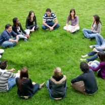 happy group of friends in a circle outdoors in a park